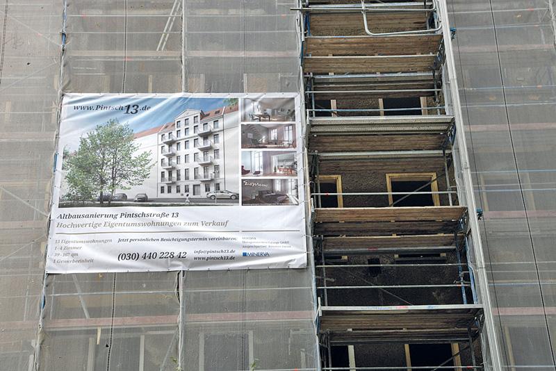Plakat an Baugerüst: Wohnungen zu verkaufen