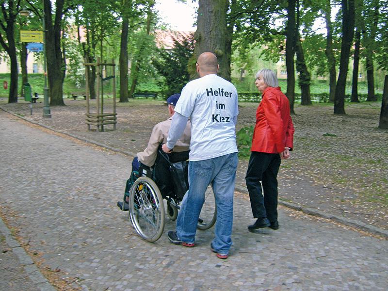 Helfer im Kiez, der einen Mann im Rollstuhl schiebt