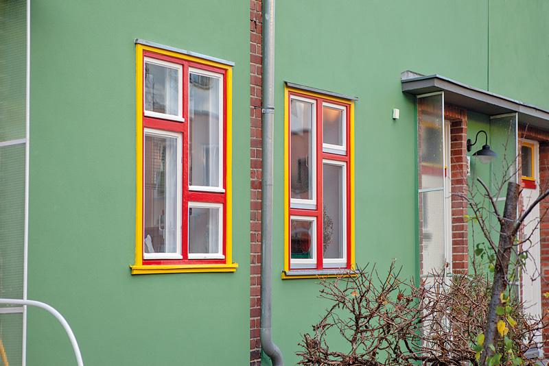 Grüne Fassade mit farbig abgesetzten Fensterrahmen