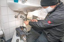 Klempner mit Maske bei der Waschbeckenmontage