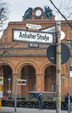 Straßenschild ,Anhalter Straße' mit Bahnhofsportal im Hintergrund