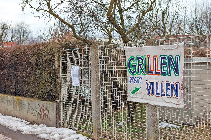 Protestplakat am Zaun: Grillen statt Villen