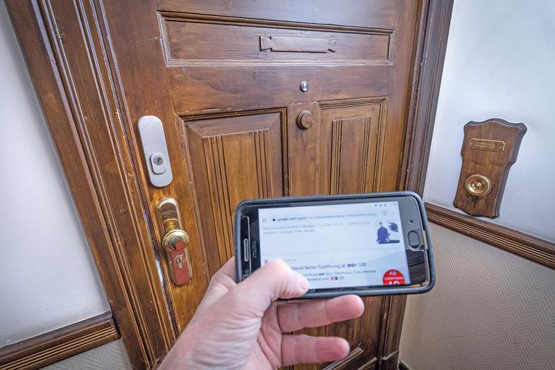 Smartphone-Eingabe vor verschlossener Wohnungstür